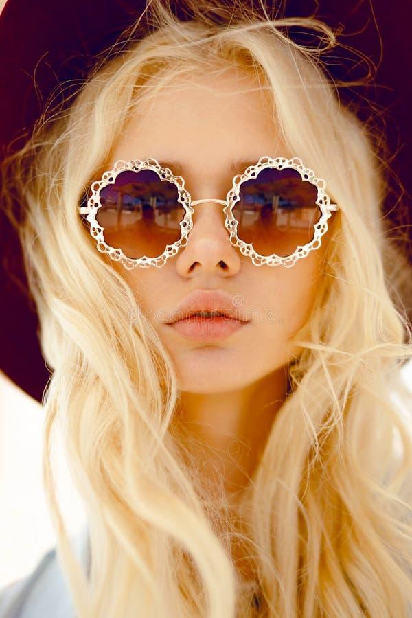 Schönheitsporträt einer sexy Blondine mit runden Blumenbrillen, große Lippen, gewelltes Haar und Burgunder-Hut, Kamera betrachten stockbild