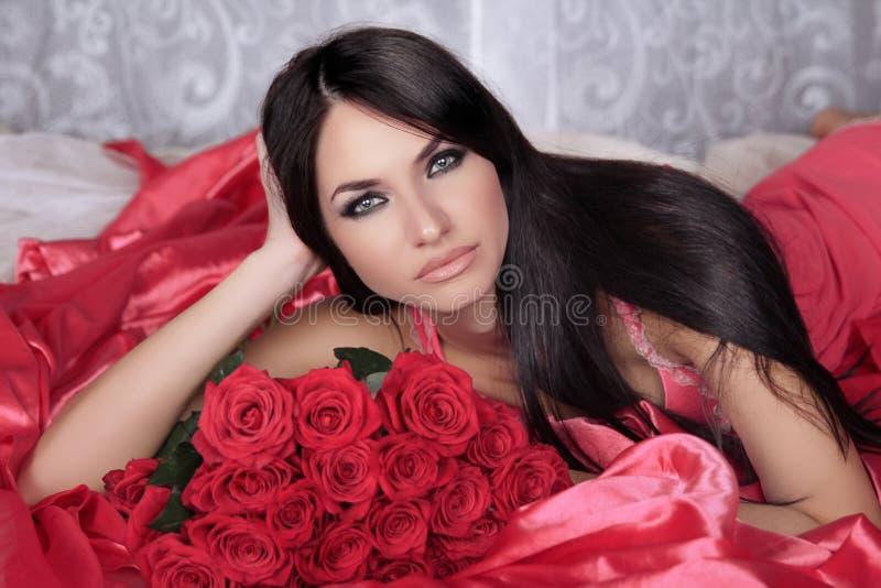 Schönheitsporträt. Erstaunliche Brunettefrau mit den roten Rosen, die an liegen lizenzfreie stockbilder