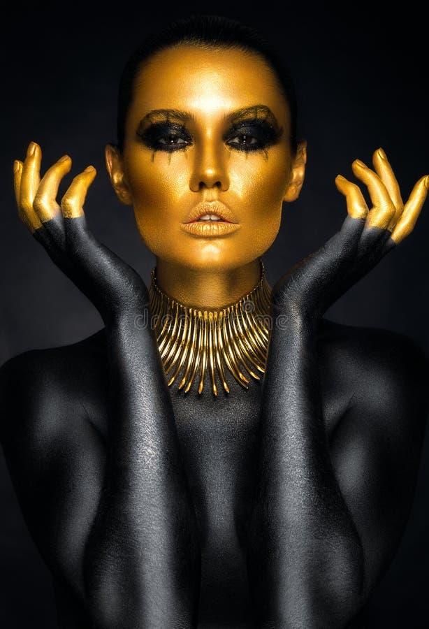 Schönheitsporträt im Gold und in den schwarzen Farben stockfoto