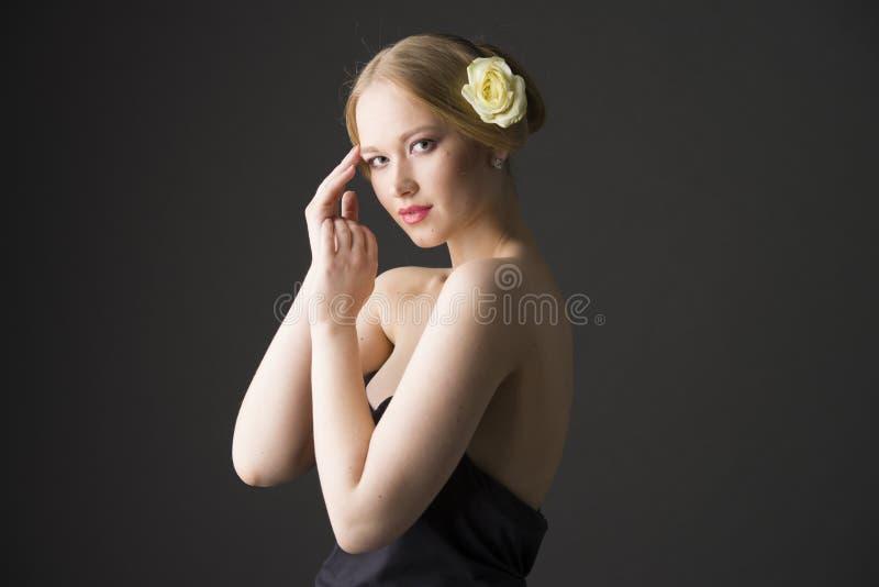 Schönheitsporträt Junge plus Größenblondine mit Gelbrose in ihrem Haar lizenzfreies stockbild
