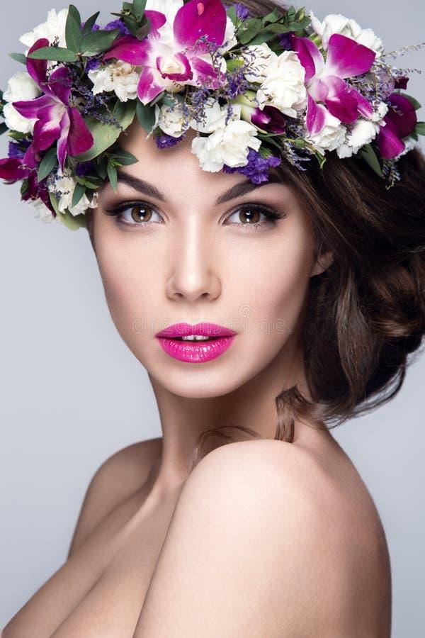 Schönheitsporträt mit Blumen auf Kopf lizenzfreies stockbild