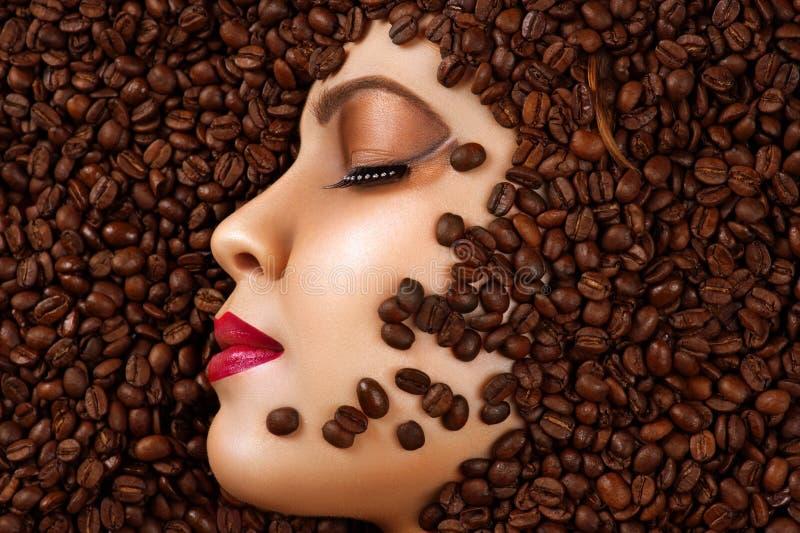 Schönheitsprofilgesicht mit Make-up in den Kaffeebohnen lizenzfreie stockbilder