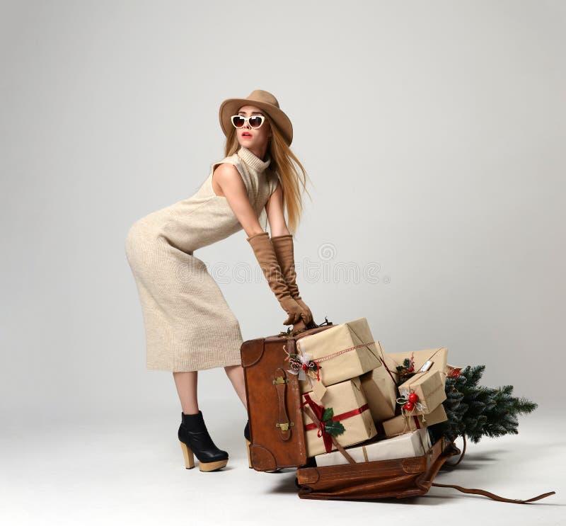 Schönheitsreisender im Hut mit der großen offenen ledernen Retro- Tasche voll von den Weihnachtsgeschenkgeschenken lizenzfreie stockfotografie