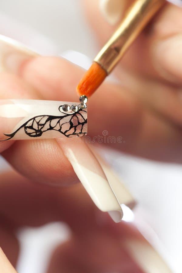 Schönheitssalon: Kleben der Kristalle auf Nagel stockfotografie