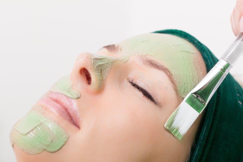 Schönheitssalon. Kosmetiker, der Gesichtsmaske am Frauengesicht anwendet. stockfoto
