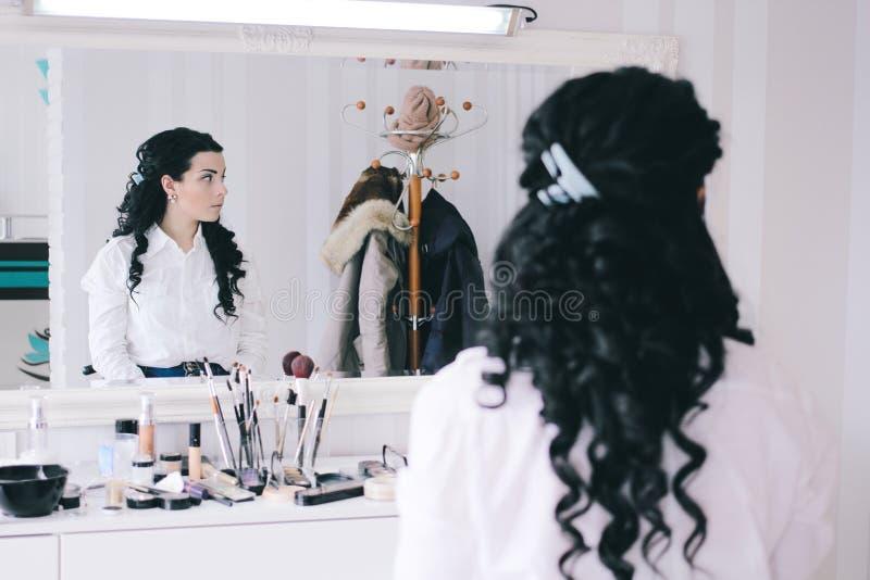Schönheitssalon, Mädchen mit dem langen schwarzen Haar sitzt am Spiegel im Th lizenzfreie stockfotografie