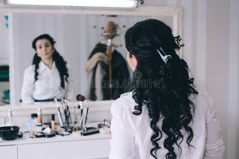 Schönheitssalon, Mädchen mit dem langen schwarzen Haar sitzt am Spiegel im Th stockfotos