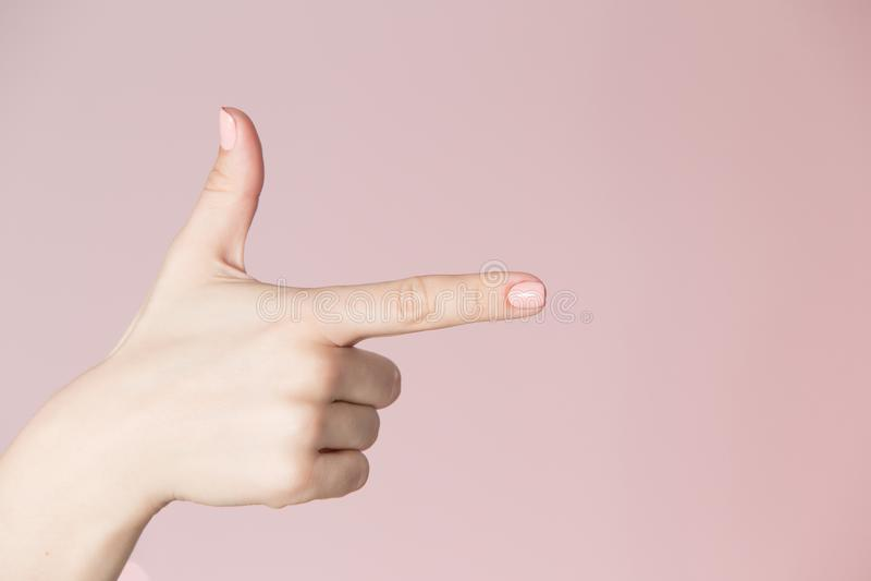 Schönheitssalon-Standortthema Frauenhand mit der rosa Maniküre, die Gewehrzeichen zeigt lizenzfreies stockfoto