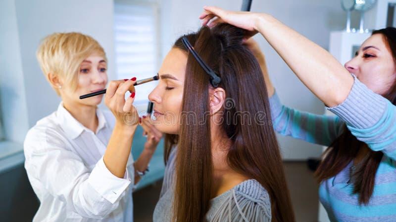 Schönheitssalonspezialisten, die Berufsmake-up und Frisur für junge brunette Frau tun lizenzfreies stockfoto