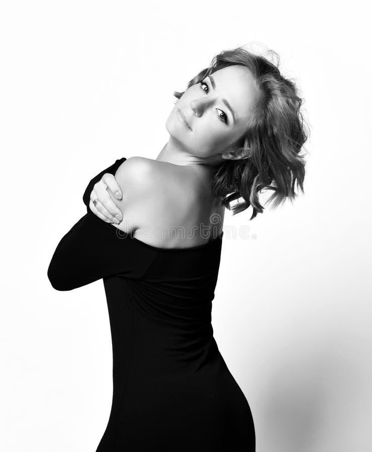 Schönheitsschauspielerin mit glücklichen Gesichtsgefühlen des gelockten Haares im schwarzen Kleid, welches das Lächeln aufwirft R stockfotos