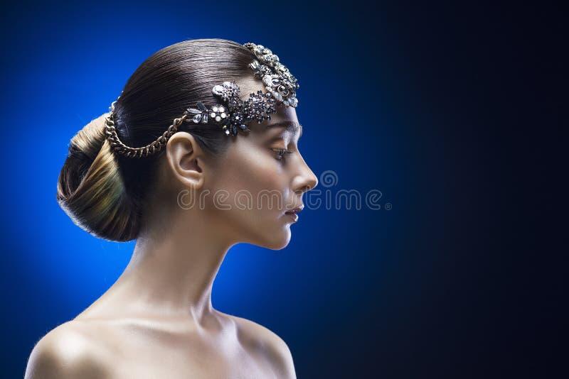 Schönheitsseitenporträt der jungen Frau mit einer genauen Frisur und der Verzierung im Haar auf einem blauen Steigungshintergrund stockbild