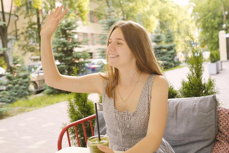 Schönheitssitzen, -lächeln und -wellen ihre Hand, die in einem Café im Freien ist Mahlzeit des strengen Vegetariers und Detoxkonz stockbild