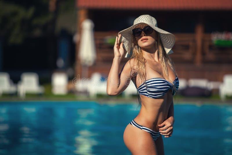 SchönheitsSwimmingpool-Sommerferien summertiA schöne junge Frau in der Badebekleidung am Poolside steht stockfotos