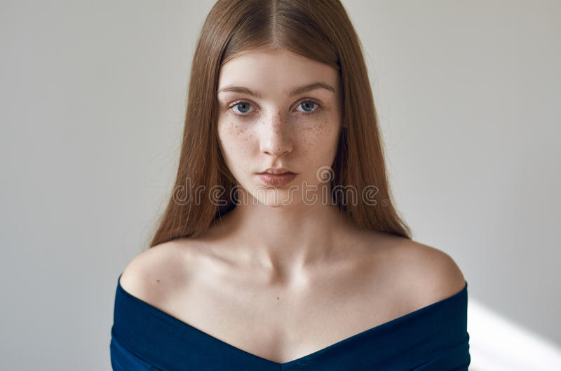 Schönheitsthema: Porträt eines schönen jungen Mädchens mit Sommersprossen auf ihrem Gesicht und dem Tragen eines blauen Kleides a lizenzfreie stockbilder