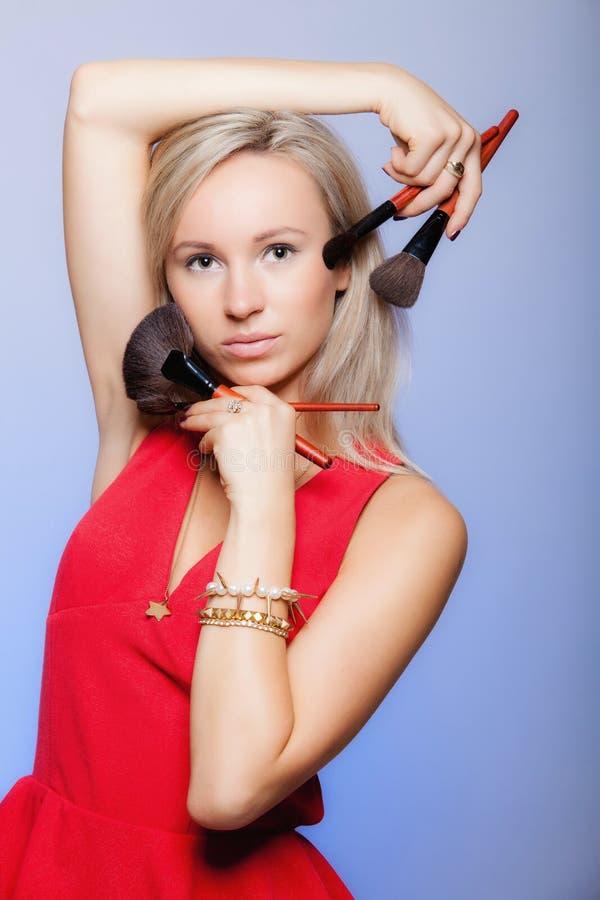 Schönheitsverfahren, Frau hält Make-upbürsten nahe Gesicht lizenzfreies stockfoto
