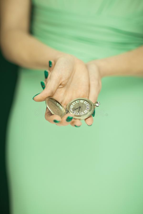 Schönheitszahl, Brautjungfer im hellgrünen Kleid, das Weinlesetaschenuhr hält lizenzfreie stockfotos
