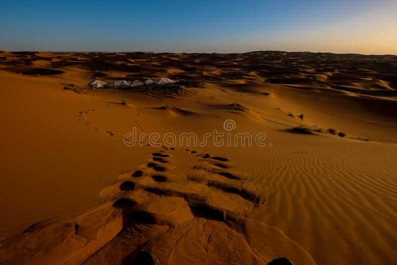 Schönschöne Fußabdrücke in Sanddüne mit weißen Zelten in der Ferne und einem klaren Himmel lizenzfreies stockbild