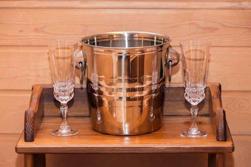 Schöpfen Sie für das Abkühlen einer Flasche und zwei Glasweingläser stehen auf einem hölzernen Regal lizenzfreie stockbilder