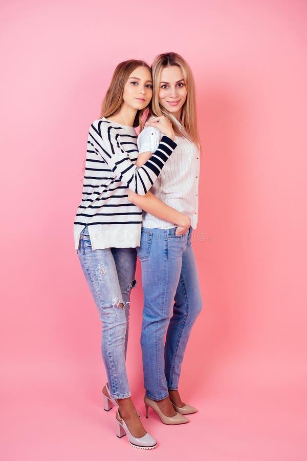 Schöschöne und lächelnde Mutter und Tochter in Jeans und stilvolle High-Heels auf rosa Hintergrund in den rosa Hintergrund posier lizenzfreie stockfotos