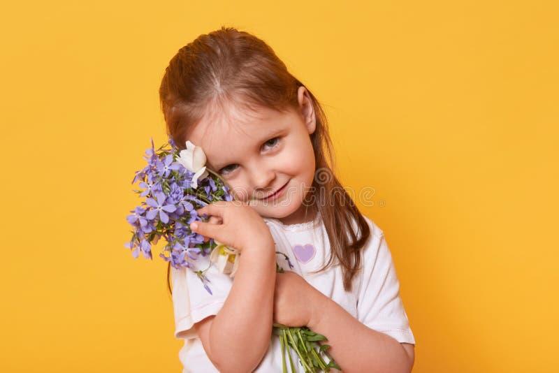 Schüchterne aber schöne lächelnde tragende weiße zufällige Stellung T-Shirt des Mädchens, die über hellem gelbem Studiohintergrun lizenzfreie stockbilder