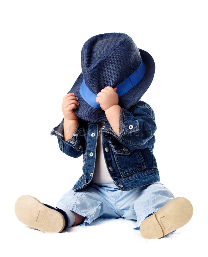 Schüchternes Baby, das hinter Hut sich versteckt lizenzfreie stockfotos