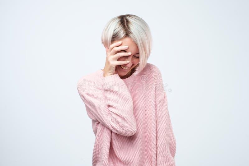 Schüchternes Mädchen mit dem kurzen gefärbten Haar lächelnd mit den Händen auf Gesicht lizenzfreie stockfotos