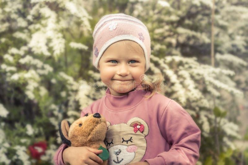 Schüchternes nettes Kindermädchen mit Blumenhintergrundkonzeptes des Porträts des Spielzeugs lächelndem glücklichem Kindheitslebe lizenzfreie stockbilder