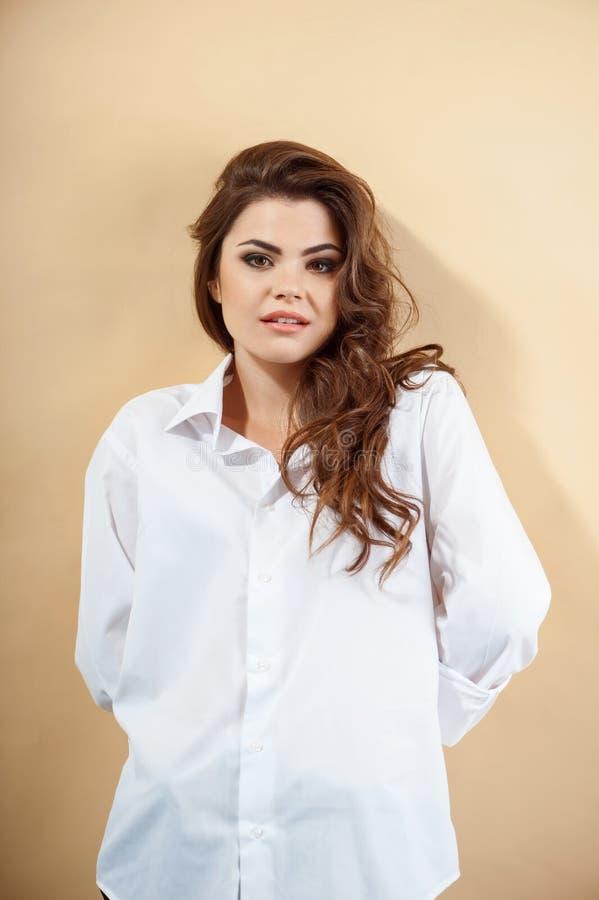 Schüchternes schönes junges Mädchen in der weißen Bluse stockfoto