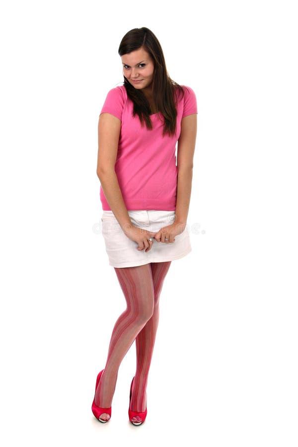 Schüchternes schönes Mädchen mit langem Fahrwerkbeinisolat auf Weiß stockbilder
