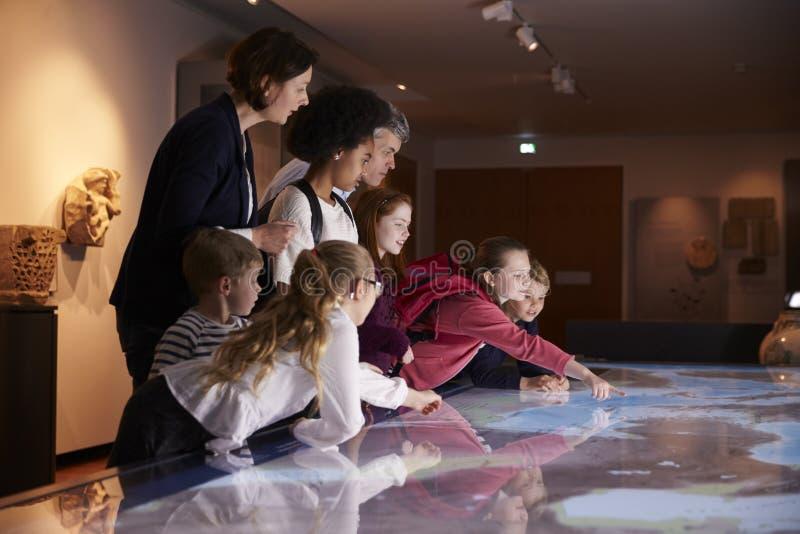 Schüler auf Schulexkursion zum Museum, das Karte betrachtet lizenzfreies stockbild