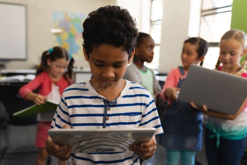 Schüler, der auf digitaler Tablette im Klassenzimmer studiert stockfoto