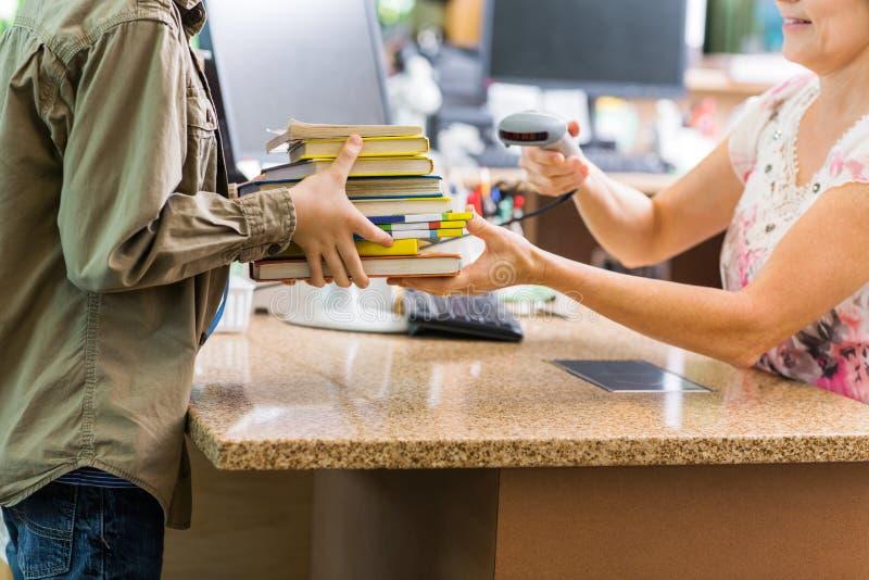 Schüler, der Bücher am Bibliotheks-Zähler hält lizenzfreies stockbild