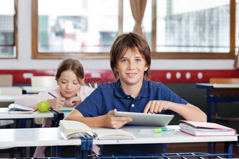 Schüler, der Digital-Tablette im Klassenzimmer verwendet lizenzfreie stockfotos