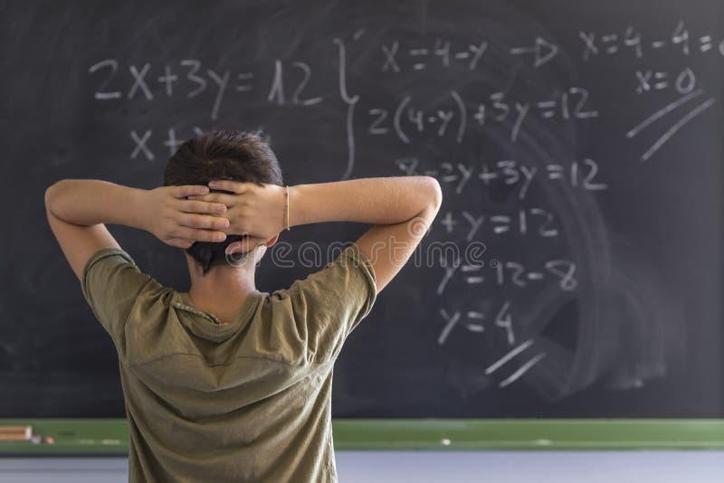 Schüler, der ein Problem auf einer Tafel löst lizenzfreie stockfotografie