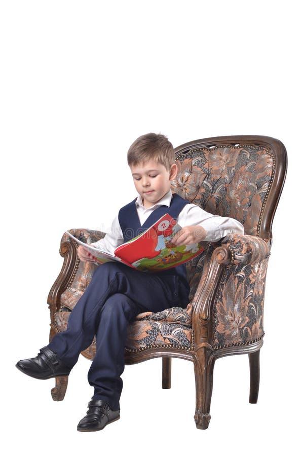 Schüler, der in einem Antike-entworfenen Stuhl- und Lesebuch sitzt lizenzfreies stockbild
