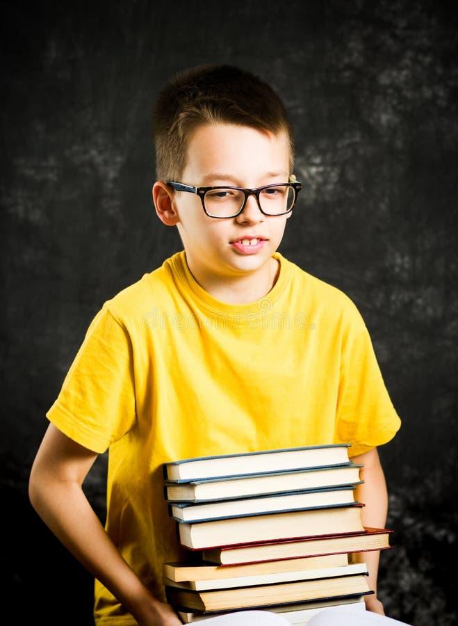 Schüler, der einen großen Stapel von Büchern anhebt stockfotografie