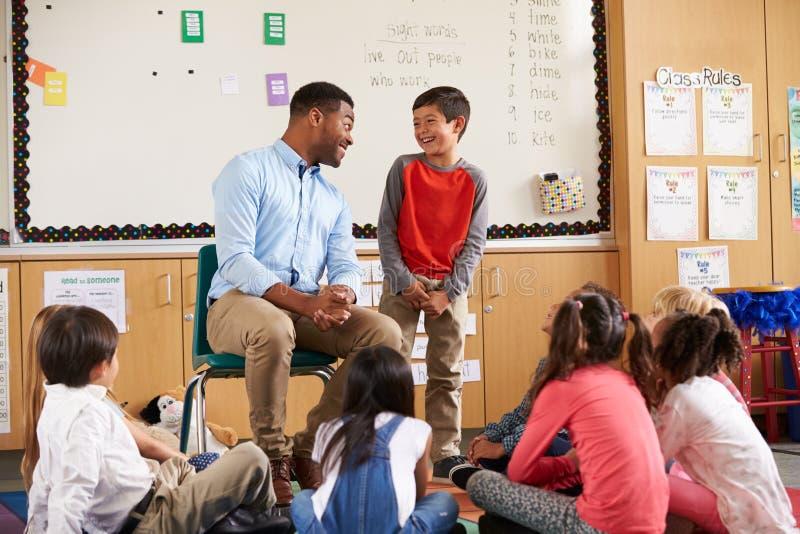 Schüler an der Front der grundlegenden Klasse sprechend mit Lehrer stockfoto