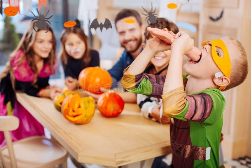 Schüler, der gelbe Augenmaske für Halloween versucht süßes Handplätzchen trägt lizenzfreie stockfotos