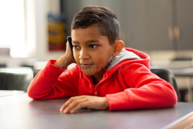 Schüler, der am Handy am Schreibtisch in einem Klassenzimmer spricht stockbild