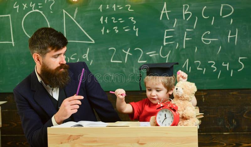 Schüler, der hometask mit Vater tut und in Arbeitsbuch, Tafel auf Hintergrund schreibt Vater, der hometask, Hilfen überprüft lizenzfreies stockfoto