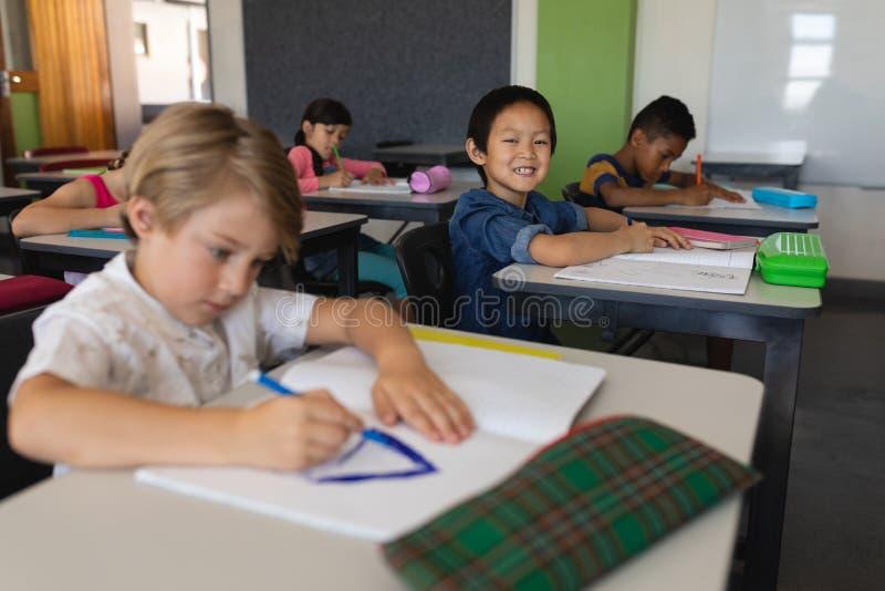 Schüler, der Kamera beim Studieren im Klassenzimmer betrachtet stockfotografie