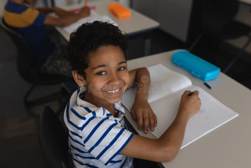Schüler, der Kamera beim Studieren im Klassenzimmer betrachtet stockfotos