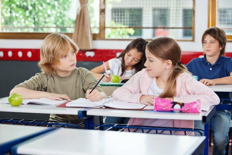 Schüler, der Mädchen beim Schreiben am Schreibtisch betrachtet stockbilder