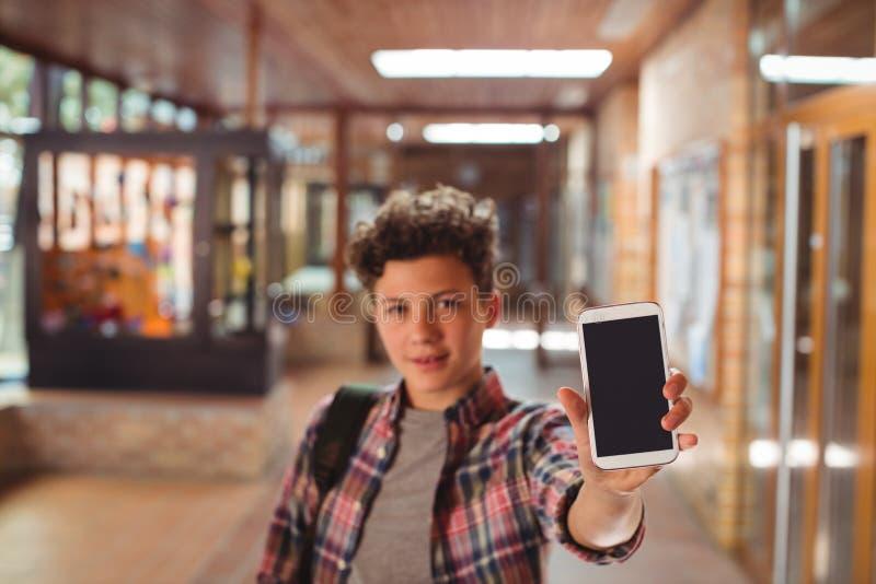 Schüler, der mit der Schultasche in der Schule zeigt Handy im Korridor steht lizenzfreie stockbilder