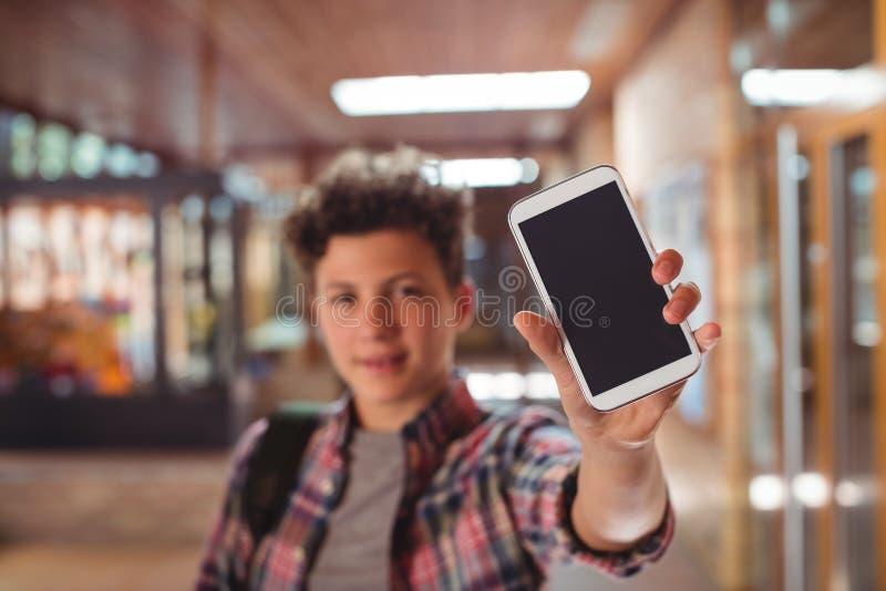 Schüler, der mit der Schultasche in der Schule zeigt Handy im Korridor steht stockfoto