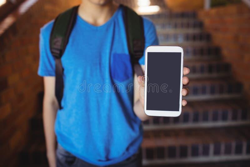 Schüler, der mit der Schultasche in der Schule zeigt Handy nahe Treppenhaus steht lizenzfreie stockbilder
