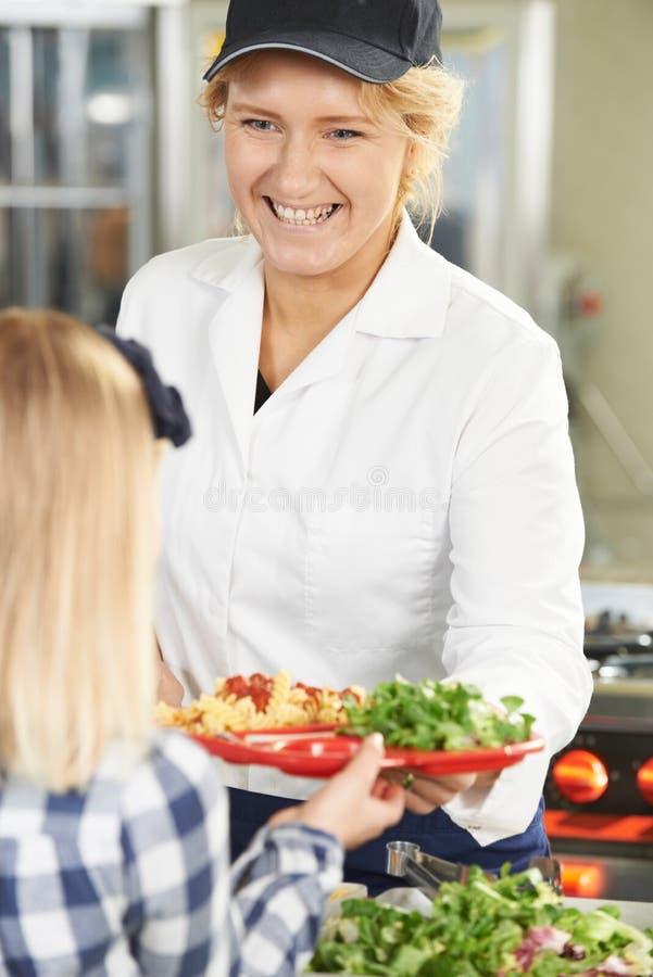 Schüler in der Schulcafeteria, die das Mittagessen von Abendessen-Dame gedient wird stockfotos