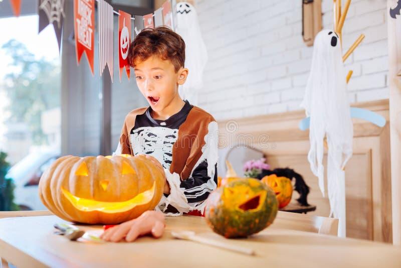Schüler, der skeleton Kostüm für Halloween steht nahen Kürbis trägt stockbild