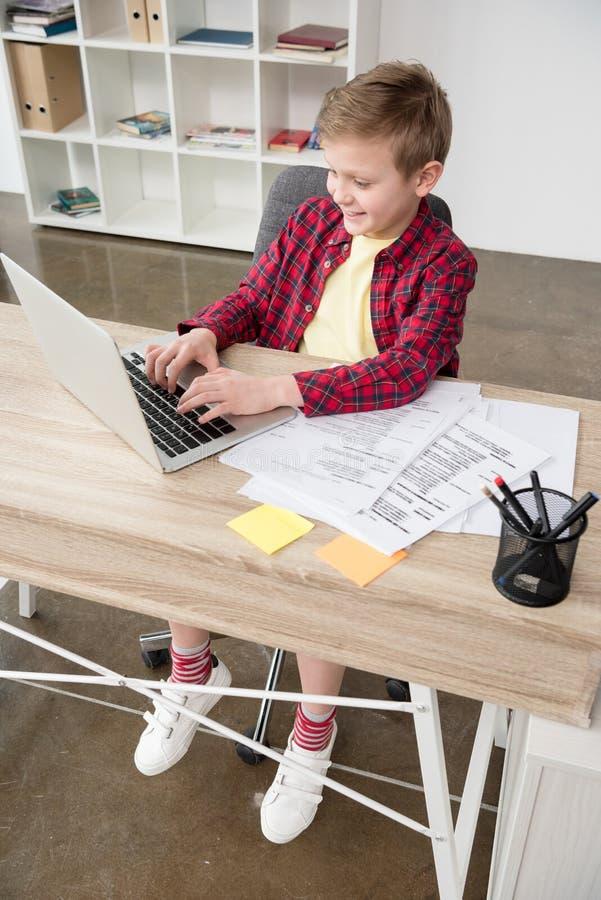 Schüler, der Vaterlaptop im Büro verwendet stockfoto