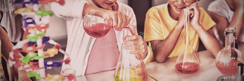 Schüler, der Wissenschaft während Mitschüler schauen sie tut lizenzfreies stockbild